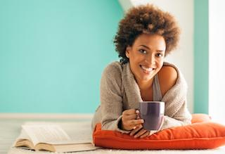 Woman sitting on pillow holding coffee cup | Dentist Edmonton