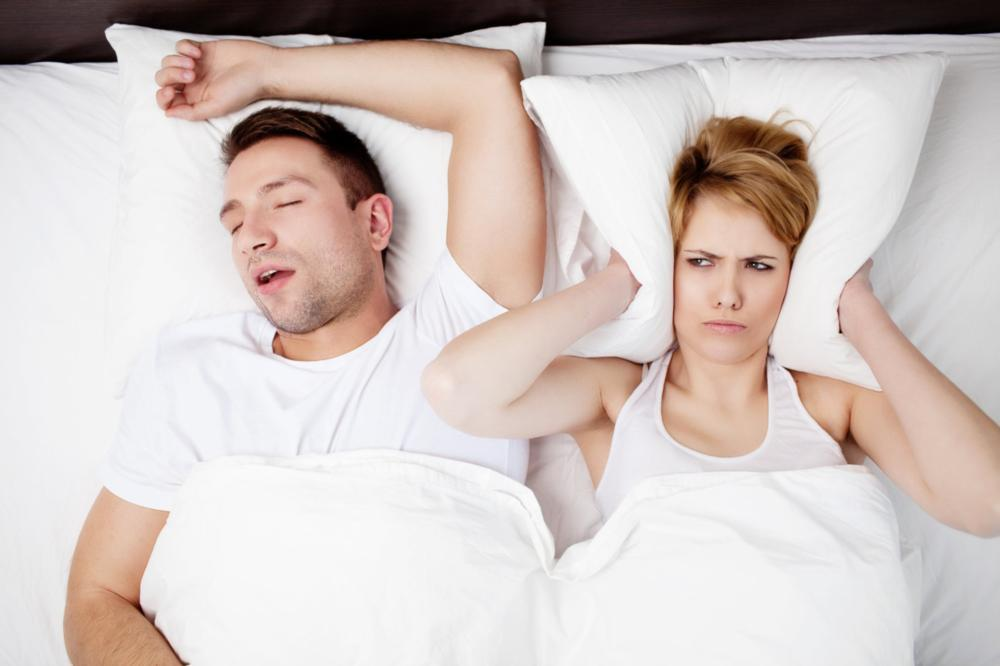 Man snoring and woman holding pillow over ears | Dentist Edmonton AB
