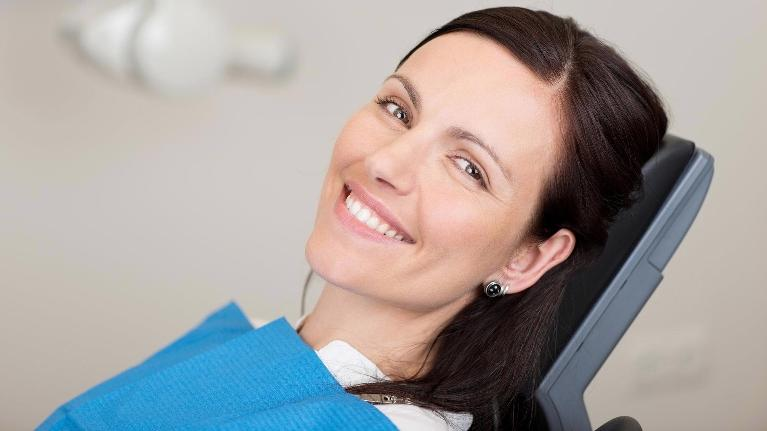 Woman smiling in dental chair | Dental Cleanings Edmonton AB