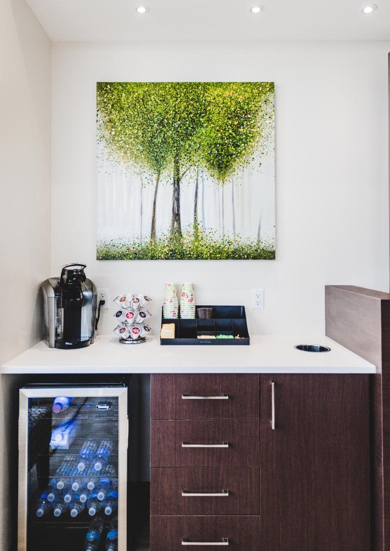 Coffee maker and fridge with water bottles | Orchards Dental